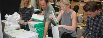 Brendon Thomas (second from left) helps employees package the first edition of The Golfer's Journal in the company's San Clemente warehouse facility. Photo: Steve Breazeale