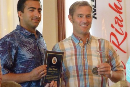 San Clemente lifeguard Sina Riahi, left, receives the Lifeguard of the Year honors with a plaque and challenge coin from City Council member Chris Hamm on Thursday, Sept. 28, at Wedgewood at the San Clemente Municipal Golf Course. Photo: Courtesy of the city of San Clemente.