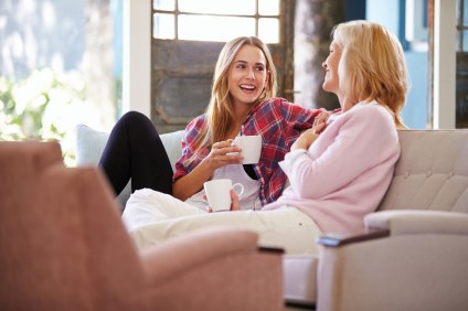 Mature Mother With Adult Daughter Relaxing On Sofa At Home