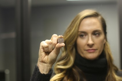 Lisa Spitzer Lawson holds a passing coin, which her business creates to be distributed among friends to show they care and to spread inspiration. Photo: Eric Heinz
