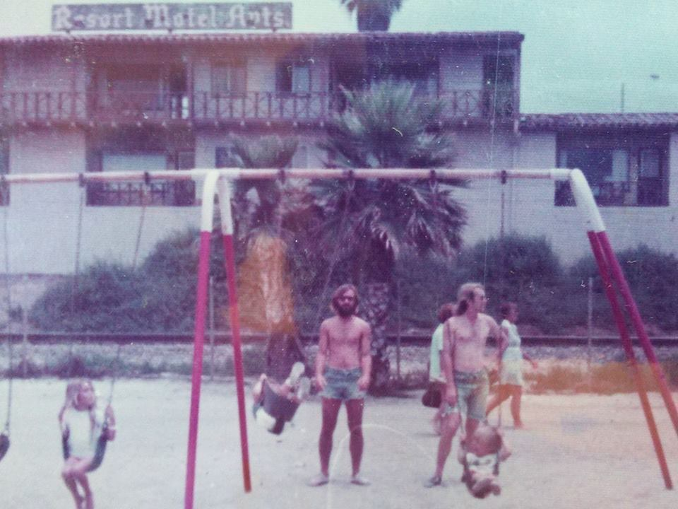 """This photo was taken in 1974 when Wyatt Marshal Dearlove was an infant. """"The Resort Motel Apts behind the swing sets on the north side of the pier 1974,"""" Dearlove said. """"My pop pushing me on the right. My godfather pushing his daughter on the left (almost out of her swing)."""" Photo: Courtesy of Wyatt Marshal Dearlove"""
