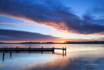 Dramatic and colorful sunrise at a jetty on a winter day.
