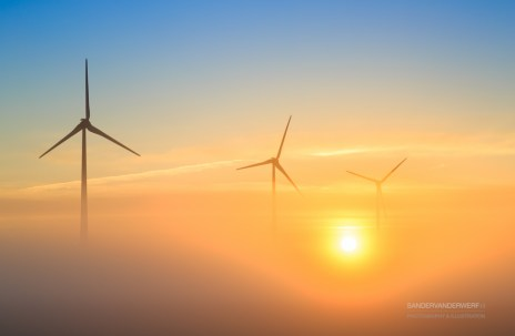 Wind turbines genrating sustainable enrgy during a foggy sunrise.