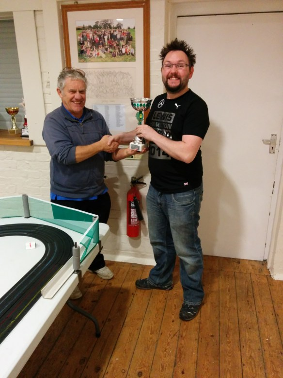2014 Combined Micro Scalextric Club Class and Super F1 Champion Paul Rose is awarded his trophy by Club founder Tony Stacey.