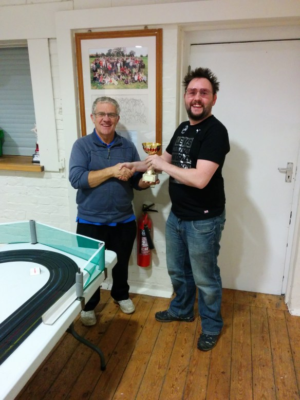 2014 Micro Scalextric Club Class Champion Paul Rose is awarded his trophy by Club founder Tony Stacey.