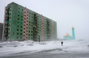 A man walks past a Soviet era housing block near the Nurd Kamal mosque in the arctic Russian city of Norilsk. Credit: Roger Bacon/REUTERS/Alamy