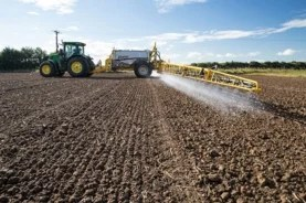 truck applying herbicide to crop