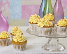 Vanilla cupcakes on a glass cake stand coloured bottles in the background