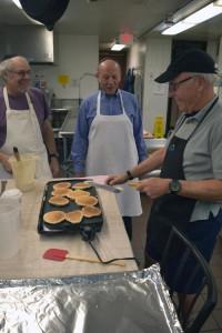 Alan Goldenberg and Bill Friedel observe Bill Sperling's pancake technique
