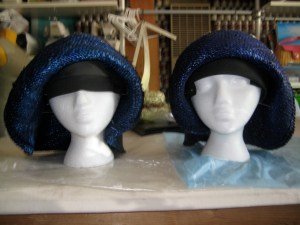 Here's the pair of freshly reblocked hats, drying on the table.  Once they're completely dry, you'll remove the pins.  Voila! Hat accomplished.  It's a good plan to spray the inside of the hat with hat sizing (a highly toxic spray that causes 16 kinds of cancer in Californian lab rats - use a ventilated area).  In a pinch, you can use any matte spray sealer inside the hat - you're really just trying to make the straws stick together a little.