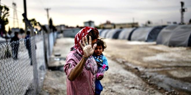 A Syrian Kurdish woman walks with her ba...A Syrian Kurdish woma