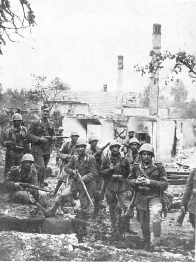 Soldati italiani posano davanti alle case bruciate di un villagio in Slovenia
