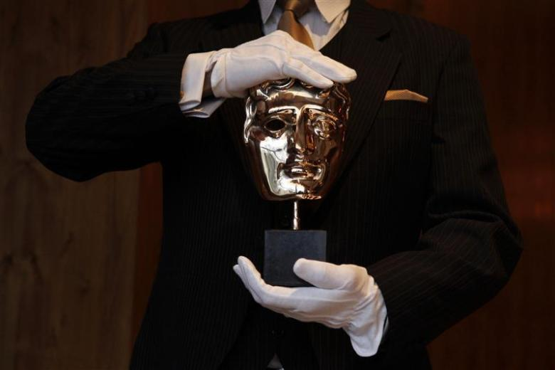 A BAFTA award mask is displayed by an employee during a media viewing at the Savoy Hotel in London