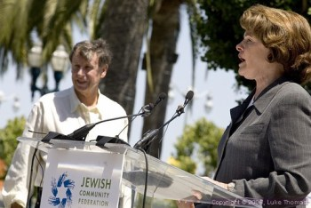 Sen. Dianne Feinstein speaks at a pro-Israel rally July 23, 2006, with her husband, Richard Blum. Blum's companies were awarded billions of dollars in military construction contracts while Feinstein chaired the Senate Subcommittee on Military Construction Appropriations. – Photo: © Luke Thomas