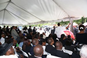 Mourners listened to the funeral service for Father Jean-Juste under a tent outside the crowded church.  Photo: Norluck Dorange