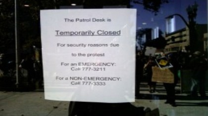 Oakland police headquarters shut down any opportunity to talk with the people the department is supposed to protect and serve for fear of October 22nd protesters, who can be seen reflected in the OPDs glass entrance door.  Photo: PNN staff