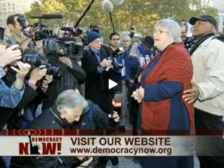 Lynne Stewart speaks to the press, backed by her husband, Ralph Poynter, shortly before going to prison. – Video frame: Democracy Now!