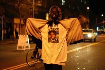 This brotha defiantly faced a wall of heavily armed OPD coming toward him on foot – with their tank – to deliver his message via the Oscar Grant T-shirt he was wearing: Rest In Power, Oscar Grant; you are gone but not forgotten! – Photo: Malaika Kambon