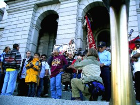 "Carrie Dann speaks at the 2005 Columbus Day Protest in Denver. The protest decried the lie that Columbus ""discovered"" America and demanded environmental and economic justice for indigenous people. According to transformcolumbusday.org, ""Before Columbus sailed the Atlantic, he was a slave trader for the Portuguese, transporting West African people to Portugal to be sold as slaves. Columbus initiated the first Trans-Atlantic slave trade"" when he stole indigenous people from the Americas to sell as slaves in Europe and stole West Africans to sell as slaves in the Caribbean."