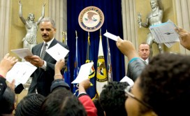 "Department of Justice employees ask their new boss, Attorney General Eric Holder, to autograph their Black History Month programs after he delivered this speech urging ""a nation of cowards"" to begin confronting the issue of racial justice. – Photo: Saul Loeb, AFP-Getty Images"