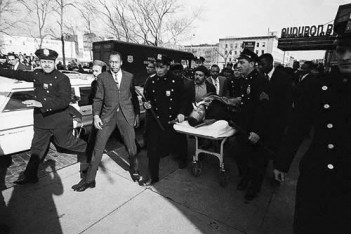 Malcolm is wheeled out of the Audubon Ballroom on a stretcher, escorted by NYPD, on the fateful day, Feb. 21, 1965.