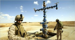Brig. Gen. John R. Allen, left, stands guard at an oil and natural gas well in the desert of Iraqs western Anbar Province, near Syria, where new deposits have recently been found. U.S. control of Iraqi natural gas as well as oil is a major factor driving the war. - Photo: Robert Nickelsberg, Getty Images, for The New York Times 