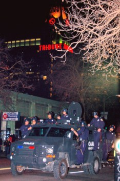 Two of the most repressive institutions demonizing Black youth are pictured here: the Oakland Tribune newspaper headquarters towering over the Oakland PD, clinging to their tank. – Photo: Brooke, IndyBay