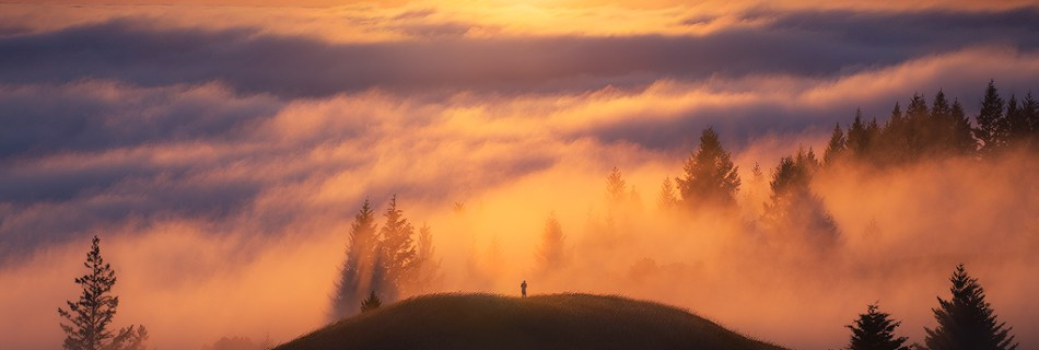 A hiker watching sunset above the fog on Mt Tamalpais near San Francisco.