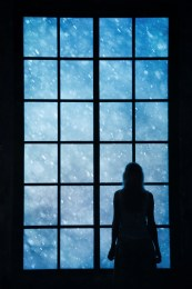 Lonely women looking at snowfall through big glass window