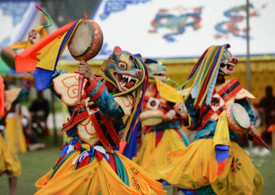Bhutanese schoolboys wear typical Bhutanese dance masks as they perform during a cultural event to celebrate the birth date of Bhutan