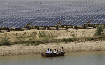 Locals on a boat pass by panels at a solar energy farm at Gunthawada in Gujarat state, about 175 kilometres north of Ahmadabad, India. There are growing calls for increased use of renewable energy resources in India. (Photo: AAP).