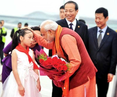 India's Prime Minister Narendra Modi receives a floral bouquet from a young Chinese child on his arrival at Xi'an Xiangyang International Airport in Xi'an, 14 May 2015. (Photo: AAP)