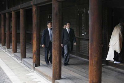 Japanese Prime Minister Shinzo Abe, second from left, is led by a Shinto priest, right, after paying respect for the war dead at Yasukuni Shrine in Tokyo (Photo: AAP)