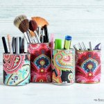 Use fabric covered tin cans to organize makeup and brushes
