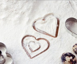 Ingredients for baking - eggs, flour, wheat. Kitchen utensils. Heart-shaped cookie cutters. Valentine day or mother day background.