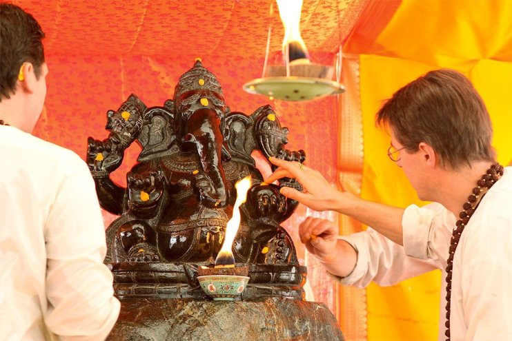 Swami Brahmananda puts tilaks on a sacred murthi of Lord Ganesh