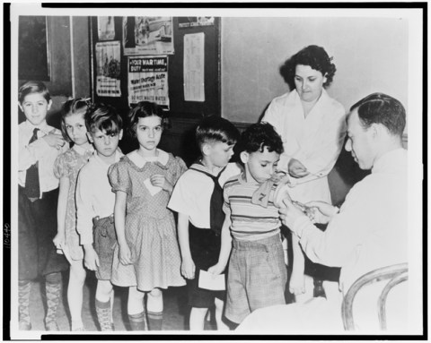 Line of New York City children receiving vaccines during World War II.