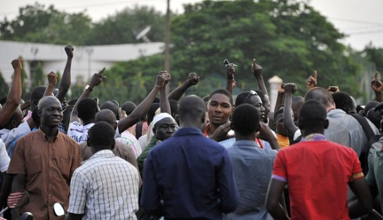 """People gather at the Place de la Nation in Ouagadougou on September 16, 2015, few hours after Burkina Faso's interim President and Prime Minister were detained at the presidential palace by guards loyal to ousted leader Blaise Compaore, the speaker of parliament said on September 16. Members of Compaore's Presidential Security Regiment (RSP) """"burst into the cabinet room at 2:30 pm and kidnapped the president of Burkina Faso Michel Kafando and Prime Minister Isaac Zida, and two ministers (Augustin Loada and Rene Bagoro),"""" interim parliament speaker Cheriff Sy said today. AFP PHOTO / AHMED OUOBA        (Photo credit should read AHMED OUOBA/AFP/Getty Images)"""