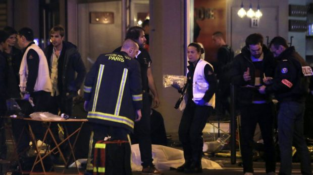 Police officers and rescue workers gather around a victim outside a Paris restaurant on Friday