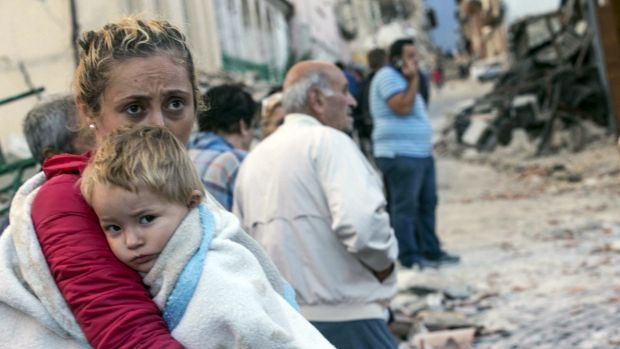 A woman holds a child as they stand in the street following an earthquake, in Amatrice, Italy.