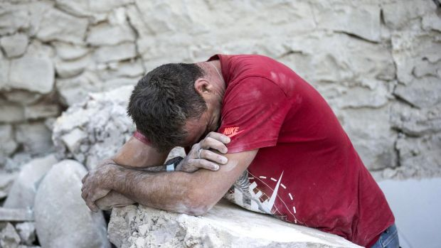 A man leans on rubble following an earthquake in Amatrice Italy.