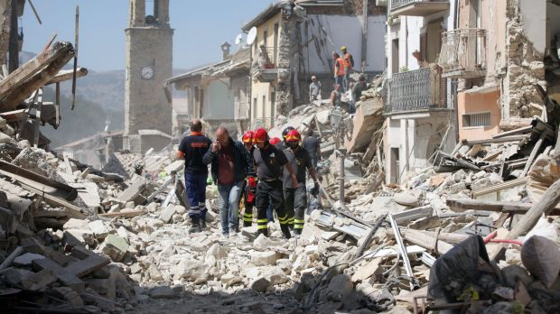 Rescue workers search for survivors in the rubble following an earthquake in central Italy.