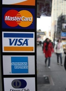 Pedestrians walk past credit cards signs on a deli doorway in New York. President Barack Obama will tell US credit card industry chieftains he will push for more regulation to shield consumers from unfair fees, punitive interest rates and predatory lending