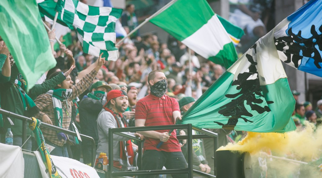 A member of the Timbers Army waves a flag in a cloud of smoke after Gastón Fernández (10) scores a goal to tie the game 1-1 in the second half. The Portland Timbers play the Chicago Fire at Providence Park in Portland, Ore. on March 16, 2014. (Michael Shaw/Emerald)