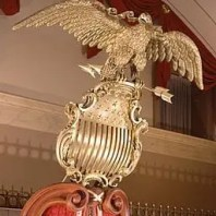 By U.S. Senate photo; sculptor unknown (Eagle and Shield (direct image URL [1]).) [Public domain], via Wikimedia Commons