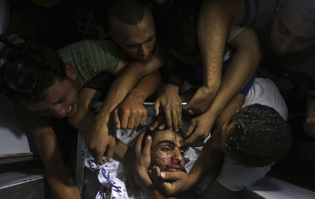 People mourn around the body of a Palestinian militant at a hospital morgue in the central Gaza Strip