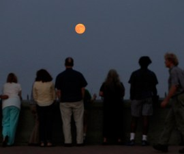 People watch a full moon known as a blue moon rises over the skyline of New York in in West Orange, New Jersey