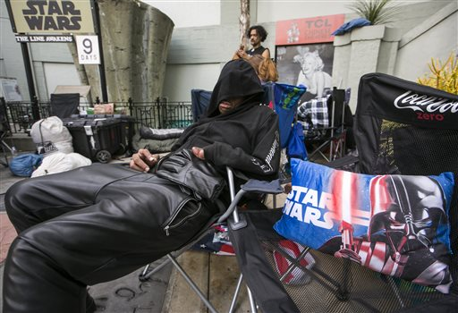 "FILE - In this Dec. 9, 2015 file photo, ""Star Wars"" fan, actor Deuce Wayne, from Virginia, rests outside the TCL Chinese Theater Imax while waiting for the premiere of ""Star Wars: The Force Awakens"" in Los Angeles. Fans waited in line outside of the historic theater as part of a charity event to raise money for the Starlight Children's Foundation. (AP Photo/Damian Dovarganes, File)"