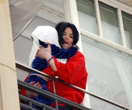 BERLIN - NOVEMBER 19:  Singer Michael Jackson appears at the balcony of the Adlon Hotel with an unidentified child November 19, 2002 in Berlin, Germany. Jackson is in Berlin with his three children to accept a lifetime achievement award.  (Photo by Olaf Selchow/Getty Images)