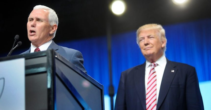 CHARLOTTE, NC - JULY 26:  Republican vice presidential candidate, Indiana Gov.  Mike Pence speaks as Republican presidential candidate Donald Trump looks on at the 117th National Convention of the Veterans of Foreign Wars of the United States as veterans strive for a photo at the Charlotte Convention Center on July 26, 2016 in Charlotte, North Carolina. One day after Democrat presidential candidate Hillary Clinton faced the same group, Trump promised a revision to health care for veterans. (Photo by Sara D. Davis/Getty Images)